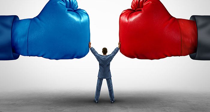 A person in a suit standing between two giant red and blue boxing gloves holding his hands up to stop them